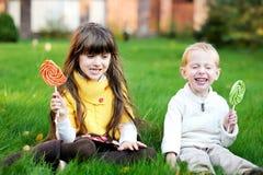 Pequeños amigos que comen los lollipops juntos en un césped fotografía de archivo libre de regalías