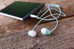 Pequeños auriculares con el teléfono móvil Imagen de archivo libre de regalías