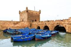 Pequeños barcos azules en el puerto de Essaouira con la fortaleza Imagen de archivo libre de regalías