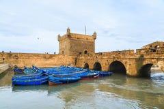 Pequeños barcos azules en el puerto de Essaouira con la fortaleza Foto de archivo libre de regalías