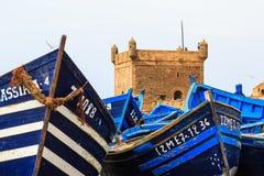 Pequeños barcos azules en el puerto de Essaouira con la fortaleza en Imagen de archivo libre de regalías