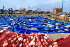 Pequeños barcos azules en el puerto de Essaouira con la fortaleza en Imagen de archivo