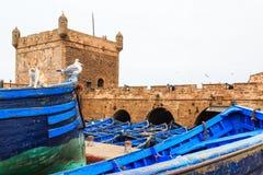 Pequeños barcos azules en el puerto de Essaouira con la fortaleza en Fotos de archivo