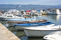 Pequeños barcos de madera en las capas del río de la ciudad Foto de archivo libre de regalías