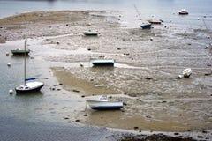 Pequeños barcos de pesca en un acceso durante la bajamar Imagen de archivo libre de regalías