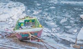 Pequeños barcos de pesca multicolores atrapados en el río congelado Danubio Foto de archivo libre de regalías