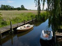 Pequeños barcos del bote de la escena tranquila en un río Imagenes de archivo