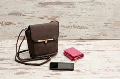 Pequeños bolso, monedero y teléfono femeninos marrones en un fondo de madera concepto de moda Fotos de archivo libres de regalías