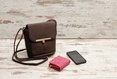 Pequeños bolso, monedero y teléfono femeninos marrones en un fondo de madera concepto de moda Imágenes de archivo libres de regalías