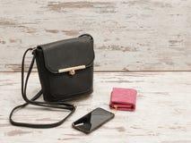 Pequeños bolso, monedero y teléfono femeninos negros en un fondo de madera Imagen de archivo