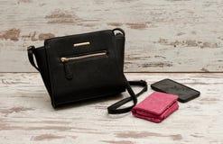 Pequeños bolso, monedero y teléfono femeninos negros en un fondo de madera concepto de moda Fotografía de archivo libre de regalías