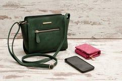 Pequeños bolso, monedero y teléfono femeninos verdes en un fondo de madera concepto de moda Fotos de archivo