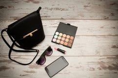 Pequeños bolso, sombra de ojos, gafas de sol, teléfono y lápiz labial negros de las señoras en fondo de madera Concepto de la man Foto de archivo