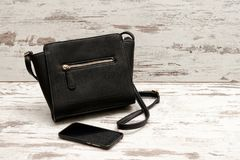 Pequeños bolso y teléfono femeninos negros en un fondo de madera concepto de moda Fotos de archivo libres de regalías