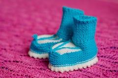 Pequeños botines hechos punto s blanco-azules del ` de los niños fotografía de archivo libre de regalías