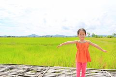 Pequeños brazos asiáticos felices del estiramiento de la muchacha del niño y relajado en los campos de arroz verdes jovenes con e imágenes de archivo libres de regalías