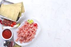 Pequeños camarones en una placa, las hojas de las lasañas y los tomates de cereza, en un fondo concreto blanco, imagenes de archivo