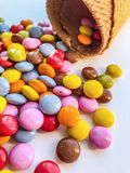 Pequeños caramelos multicolores asperjados de un cuerno de la galleta en un fondo bicolor brillante Caramelo en cono de helado stock de ilustración