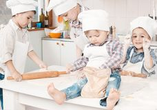 Pequeños cocineros felices que preparan la pasta en la cocina Imagen de archivo