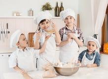 Pequeños cocineros felices que preparan la pasta en la cocina Fotos de archivo libres de regalías