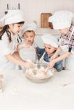 Pequeños cocineros felices que preparan la pasta en la cocina Imagen de archivo libre de regalías