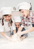 Pequeños cocineros felices que preparan la pasta en la cocina Fotografía de archivo