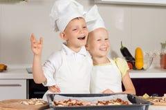 Pequeños cocineros muy felices después de cocer la pizza Foto de archivo