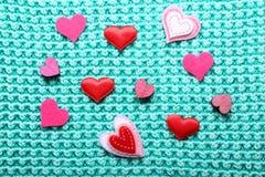Pequeños corazones en fondo hecho punto Fotos de archivo