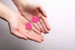 Pequeños corazones en manos femeninas en fondo de madera Fotos de archivo