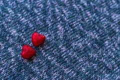 Pequeños corazones en superficies hechas punto Imagenes de archivo