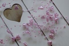 Pequeños corazones rosados en un fondo del tablero blanco Fotografía de archivo libre de regalías