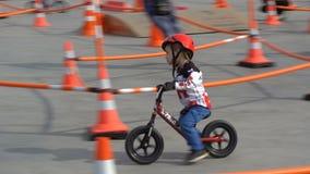 Pequeños corredores Los niños montan las bicicletas en la destilación en un parque de la ciudad almacen de metraje de vídeo
