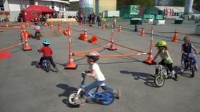 Pequeños corredores Los niños montan las bicicletas en la destilación en un parque de la ciudad almacen de video