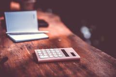 Pequeños cuaderno y calculadora blancos en vieja textura de madera del grunge fotos de archivo