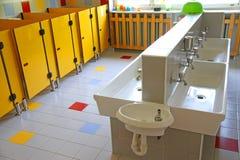 Pequeños cuartos de baño y fregaderos bajos en una escuela para los niños jovenes Foto de archivo libre de regalías