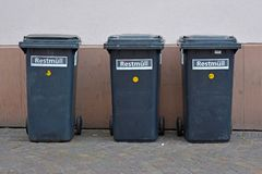 3 pequeños cubos de la basura residuales negros en las ruedas que se colocan en fila en la pared de la casa en ciudad imágenes de archivo libres de regalías