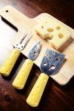 Pequeños cuchillos del queso y tajadera con el queso de emmenthal encendido Fotos de archivo