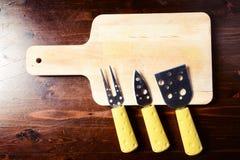 Pequeños cuchillos del queso y tajadera en la tabla de madera oscura Fotografía de archivo