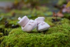 Pequeños deslizadores rosados del bebé en fondo de la hierba verde Zapatos rojos del cabrito fotografía de archivo