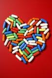 Pequeños dulces coloridos del caramelo sobre rojo Fotografía de archivo libre de regalías