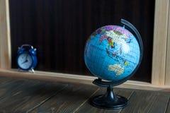 Pequeños globus, reloj y efectos de escritorio en la tabla de madera delante de la pizarra Concepto del estudio fotos de archivo