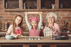 Pequeños grandchilds listos para hacer las galletas con la abuela Fotos de archivo libres de regalías