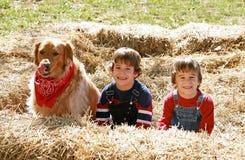 Pequeños granjeros con el perro Imagen de archivo libre de regalías