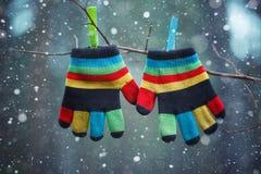 Pequeños guantes del bebé que cuelgan por un hilo en día de invierno debajo de la nieve que cae Fotos de archivo libres de regalías