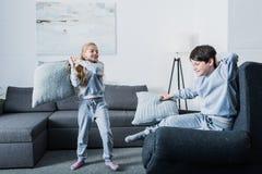 Pequeños hermanos en pijamas que luchan con las almohadas en casa Imagen de archivo