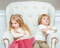 Pequeños hermanos lindos (muchacho y muchacha) que son en desacuerdo con cada othe Imagen de archivo