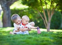 Pequeños hermanos lindos que se sientan en un césped verde que sostiene la bandera americana Fotos de archivo