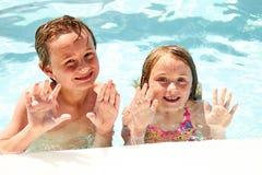 Pequeños hermanos o amigos felices que agitan en piscina Fotos de archivo libres de regalías