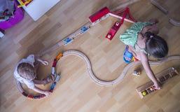 Pequeños hermanos que juegan con el tren de madera del juguete foto de archivo