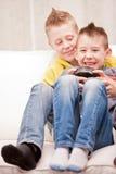 Pequeños hermanos que juegan videojuegos juntos Fotografía de archivo